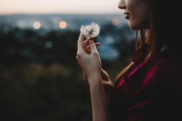 Female portrait. nature. pretty woman plays with dandelion stand Free Photo