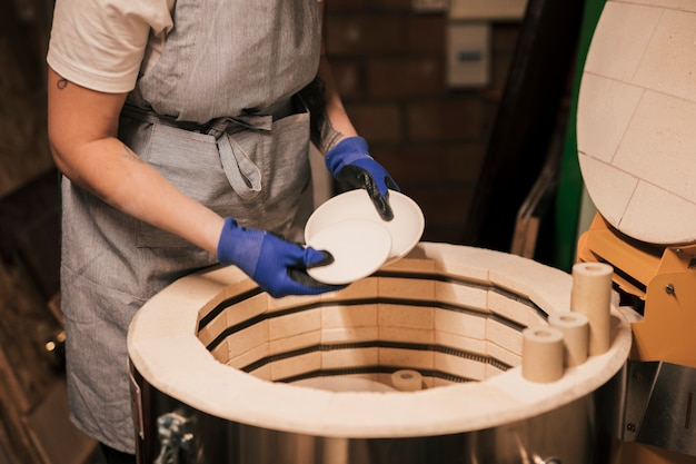 Female potter arranging the process of drying ceramics plates Free Photo