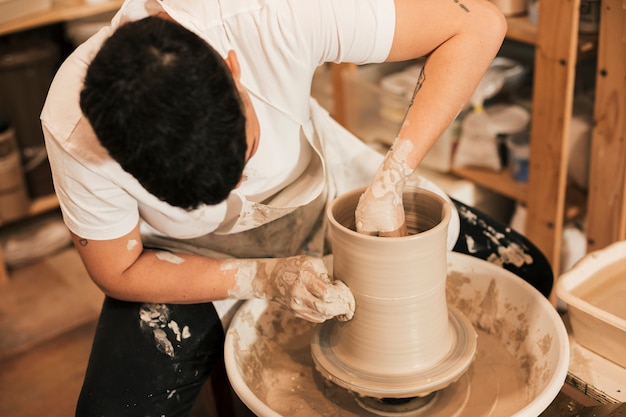 Female potter clinging the pot on pottery wheel in the workshop Free Photo