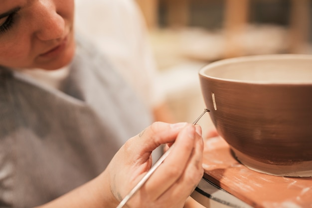 Female potter's hand drawing design on the outer surface of bowl with tool Free Photo