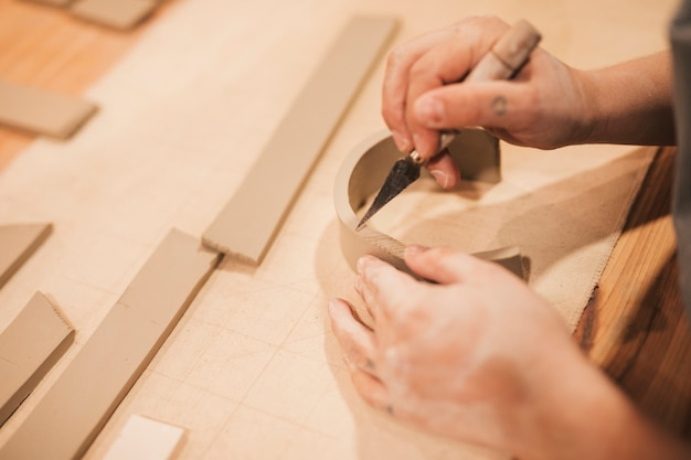 Female potter's hand engraving the clay with tools on wooden table Free Photo