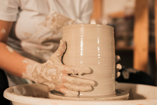 Female potter shaping pot in pottery workshop Free Photo