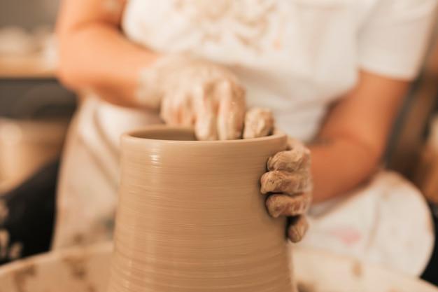 Female potter working on pottery wheel Free Photo