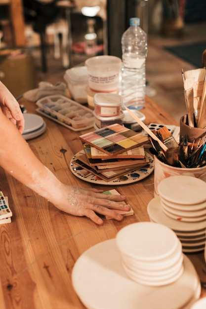 Female potters arranging the ceramic palette on wooden table Free Photo
