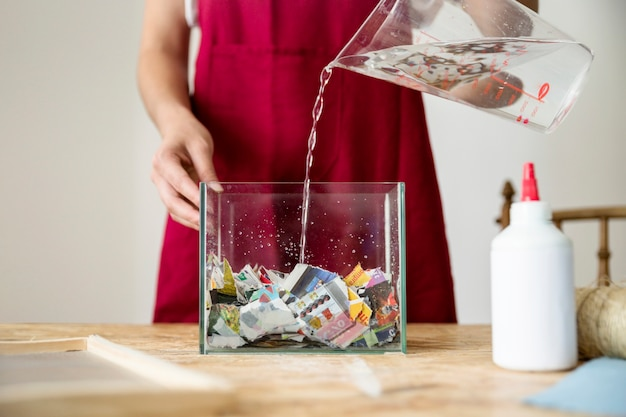 Female pouring water in container filled with paper on wooden desk Free Photo