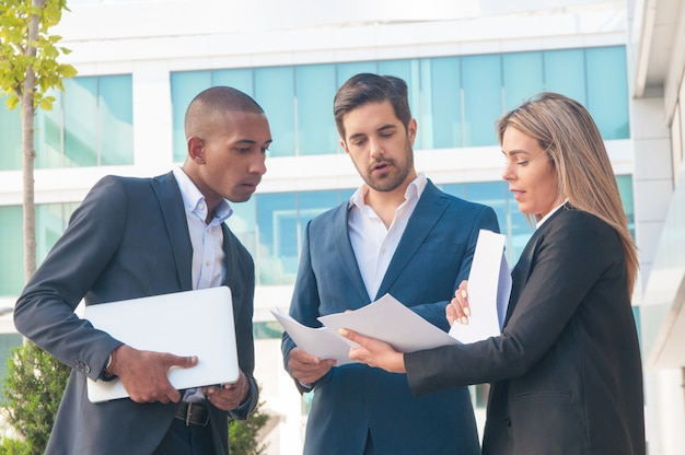 Female professional explaining reports to male colleagues Free Photo