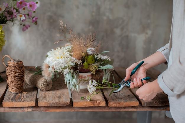 Female professional florist prepares the arrangement of wild flowers. Premium Photo