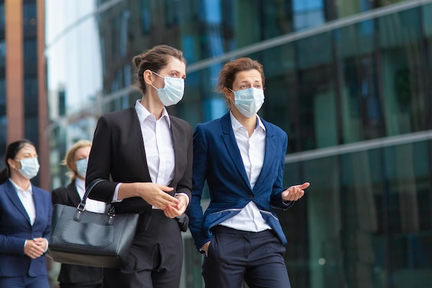 オフィススーツとマスクを身に着けている女性の専門家が会議を行い、市内で一緒に歩き、話し、プロジェクトについて話し合っています。ミディアムショット。パンデミックとビジネスコンセプト 無料写真