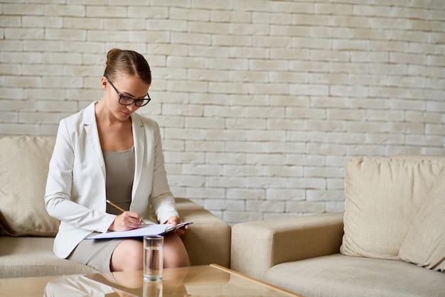 Female psychiatrist making notes Premium Photo