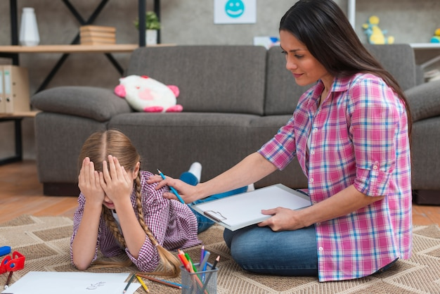 Female psychologist comforting the crying little girl Premium Photo