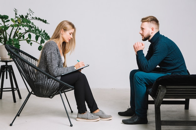 Female psychologist listening to depressed male patient and writing down notes on clipboard Free Photo
