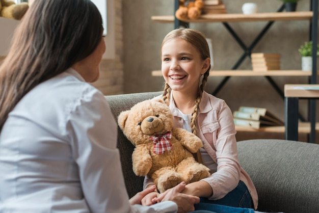Female psychologist talking with girl holding teddy bear during therapy session Free Photo