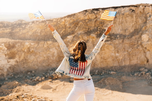 Female raising hands with flags on mountain Free Photo