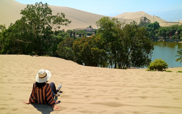 Female relaxing on the sand dune, admiring the oasis town of huacachina, ica, peru Premium Photo