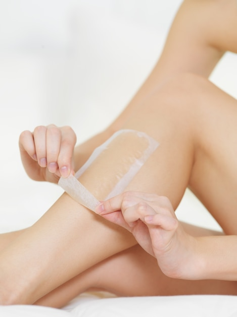 Female removing the strip of wax from legs Free Photo