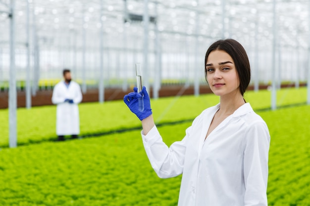 Female researcher holds a glass tube with a sample standing before plants in the greenhouse Free Photo