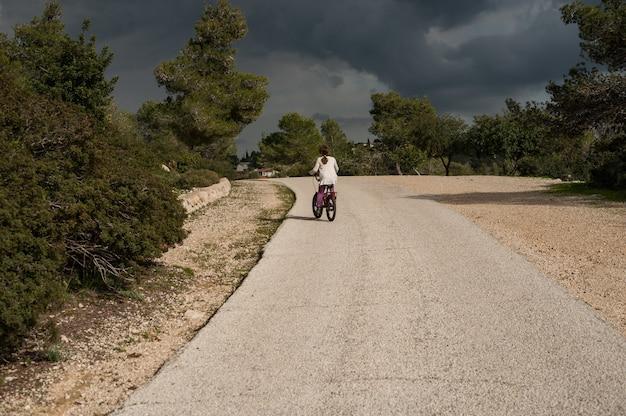 Femmina in sella a una bicicletta sulla strada durante il giorno Foto Gratuite