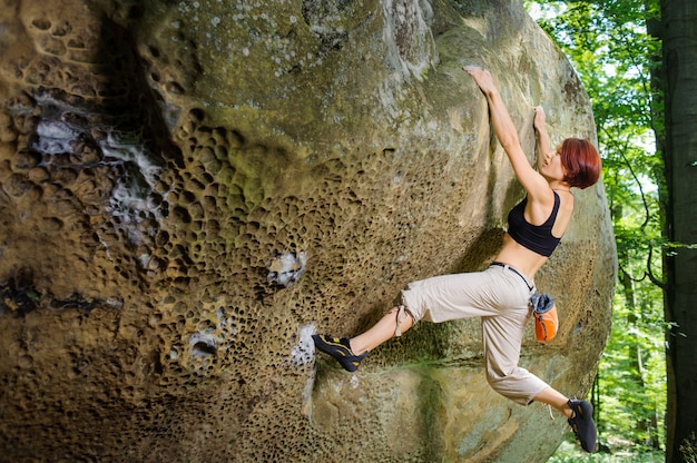 Female rock climber on her challenging way up, bouldering Premium Photo