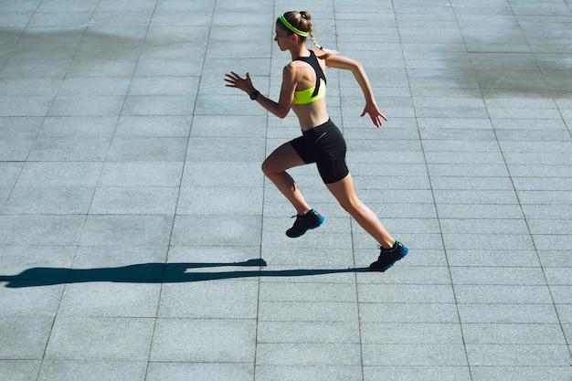 女性ランナー、アスリートが夏の晴れた日に屋外でトレーニング。 無料写真