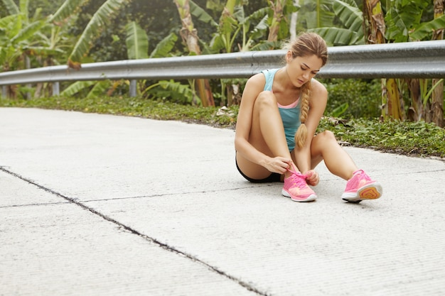 ブロンドのブレードが舗装の上に座って、ピンクのランニングシューズをひもで締めて、屋外でトレーニングをジョギングする準備をしている女性ランナー。 無料写真
