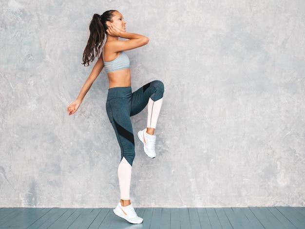 Female running in studio near gray wall Free Photo