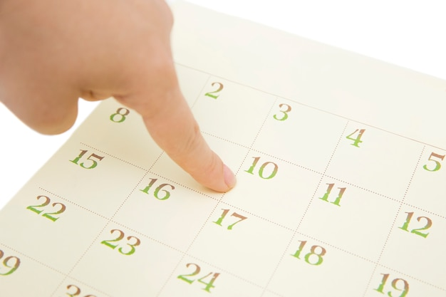 Female's finger showing date in a calendar on white background. number in the calendar Premium Photo