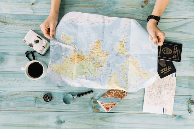 Female's hand holding map with camera; coffee; magnifying glass; map and passport on wooden plank Free Photo