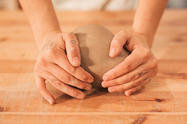 Female's hand kneading the clay on wooden table Free Photo