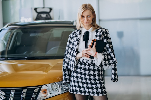 Female salesperson at a car showroom standing by the car Free Photo