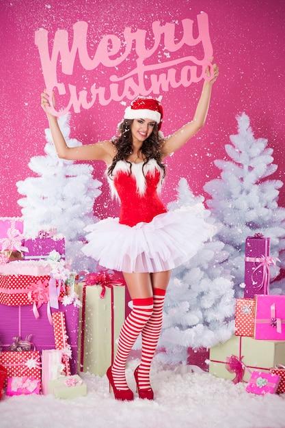 메리 크리스마스 글자와 함께 포즈를 취하는 여성 산타 클로스 무료 사진