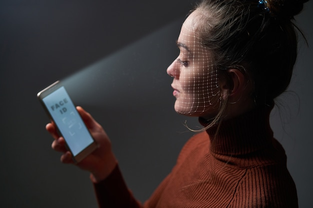 Female scans face using facial recognition system on mobile phone for biometric identification. future hi tech technology and face id Premium Photo