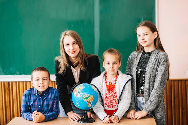 Female school teacher and students standing with globe Free Photo