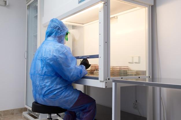 Женщина-исследователь в защитной форме и оборудовании работает с чашкой петри в лаборатории Premium Фотографии