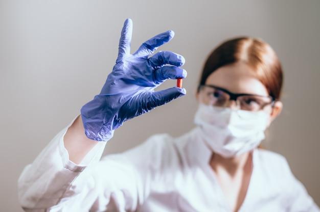 保護マスクを付けた女性科学者が薬の丸薬を見せています。斬新で革新的な治療コンセプト。健康の概念 Premium写真