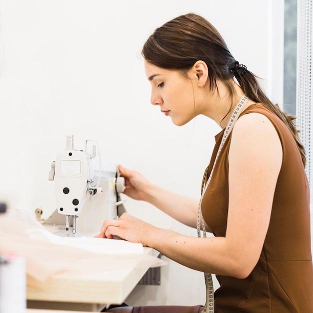 Female seamstress working on sewing machine Free Photo