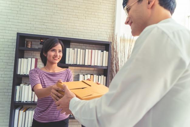 Female seller home business owner handling package to customer Premium Photo