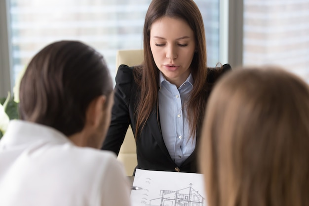 Female serious estate agent discussing house building plan with clients Free Photo