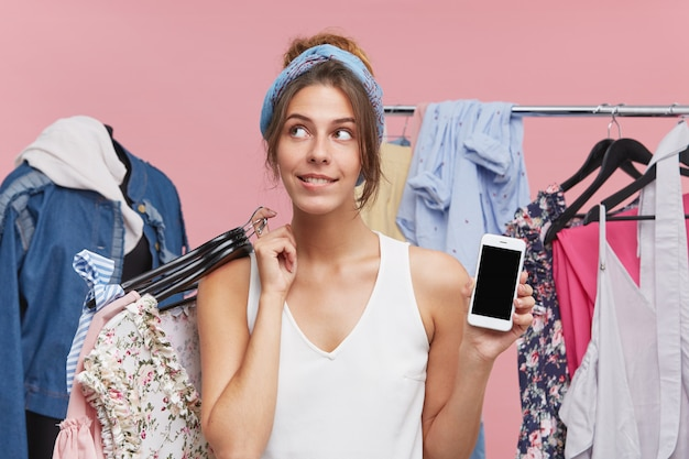 ブティックに立つ女性の買い物中毒者、多くのハンガーを試着するために服を着て、夢のような表情を脇に置いて、何をとるかを決定し、一方で現代の携帯電話を手に入れている 無料写真