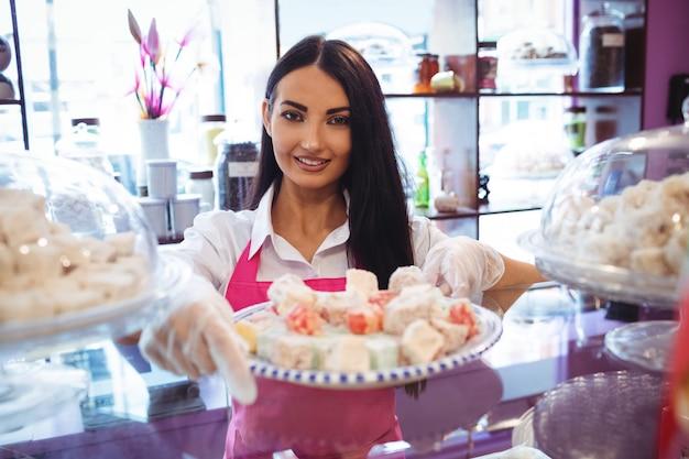 カウンターでトルコのお菓子のトレイを保持している女性の店主 無料写真