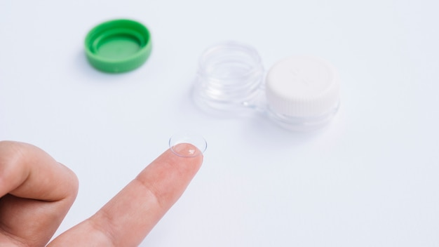 Female showing contact lenses on his finger Free Photo