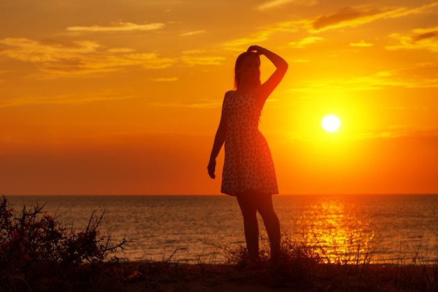 Female silhouette at sunset on the beach, hands up Premium Photo