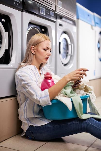 床に座って、洗濯場の洗濯室でスマートフォンを持っている洗濯機に寄りかかる女性。待っている金髪の白人女性。 Premium写真