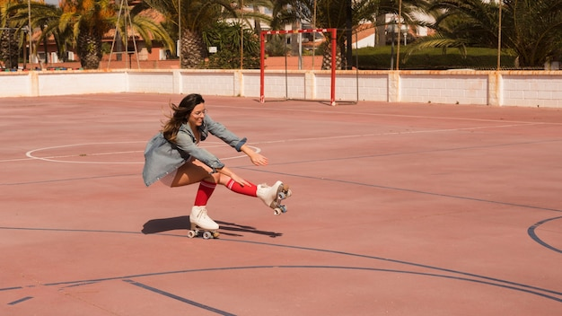 Female skater crouching and balancing on one leg in the court Free Photo