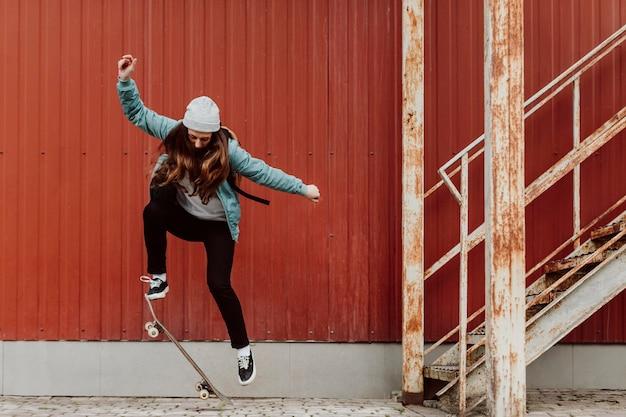 Pattinatore femminile che pratica lo skateboard all'aperto Foto Gratuite