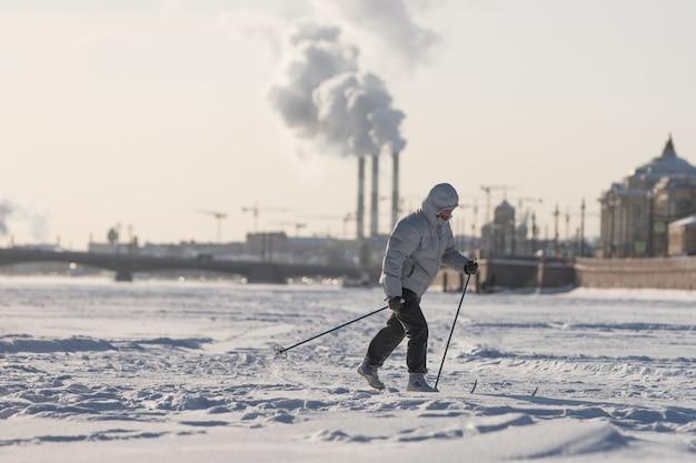 晴れた日に凍ったネヴァ川の氷の上に乗って女性スキーヤー、サンクトペテルブルクの春先、受胎告知橋の表面。都会でのウィンタースポーツ Premium写真
