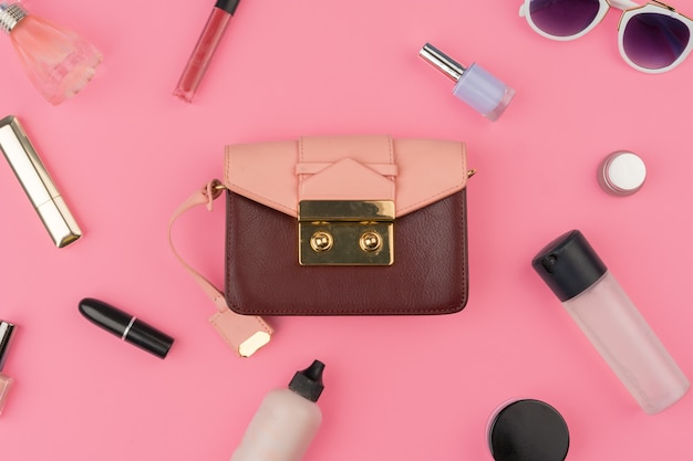 Female small handbag full of cosmetic products on bright pink background Premium Photo