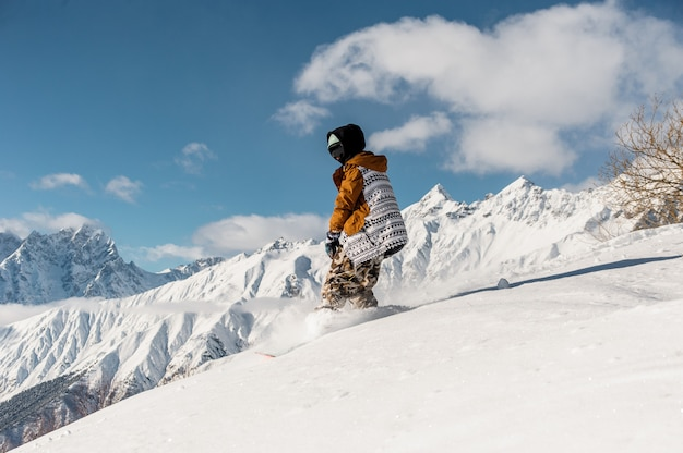 Female snowboarder in sportswear riding on the mountain slope Premium Photo