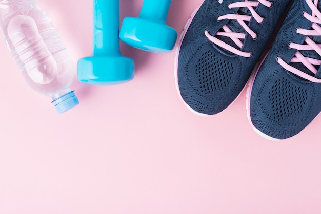 Female sport shoes, blue dumbbells and bottle of water on a pink background Premium Photo