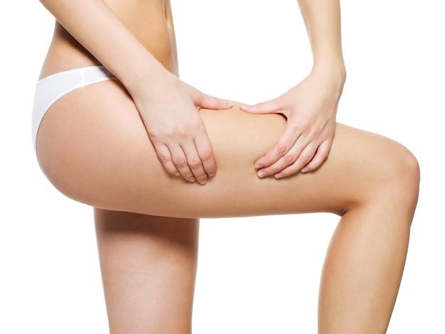 Девушка сжимает целлюлитную кожу на ногах Бесплатные Фотографии