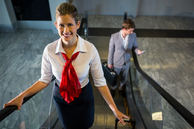 Female staff and passengers with luggage on escalator Free Photo
